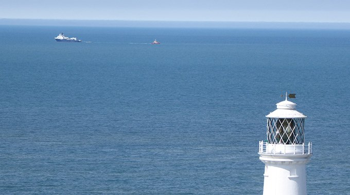 Service vessels passes the South Stack lighthouse on Holy Island while towing Minesto's GBS foundation to Holyhead Deep.